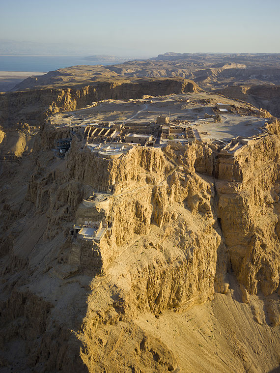 Aerial view of Masada (Hebrew מצדה), in the Judaean Desert (Hebrew: מִדְבַּר יְהוּדָה‎, Arabic: صحراء يهودا), with the Dead Sea in the distance.